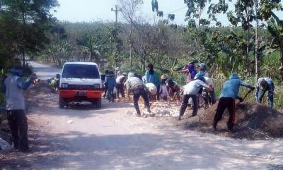 PERBAIKI: Sejumlah pekerja sedang memperbaiki jalan menuju Pabrik Gula Blora. (suaramerdeka.com/ Sugie Rusyono)
